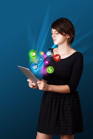 Young business woman looking at modern tablet with abstract lights and various icons photo