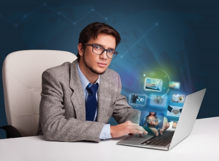 Attractive young man sitting at desk and watching his photo gallery on laptop photo