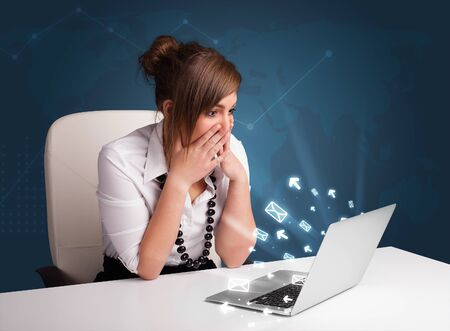 Pretty young lady sitting at dest and typing on laptop with message icons comming out Stock Photo - 18489003