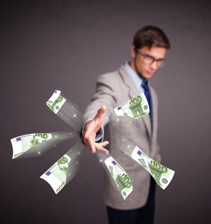 Handsome young man standing and throwing money Stock Photo - 18489718