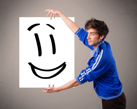 Handsome young boy holding smiley face drawing Stock Photo - 18489714