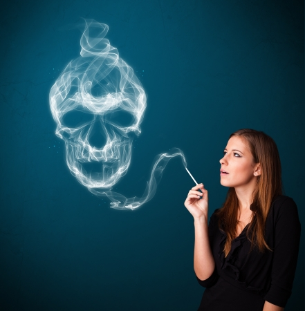 Pretty young woman smoking dangerous cigarette with toxic skull smoke Stock Photo - 18529803