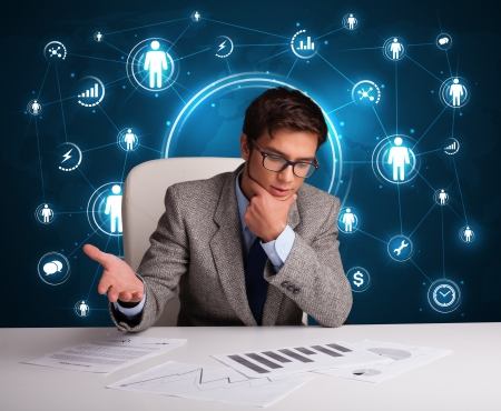 business relationship: Young businessman sitting at desc with social network icons