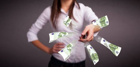 Pretty young woman standing and throwing money Stock Photo - 18529865