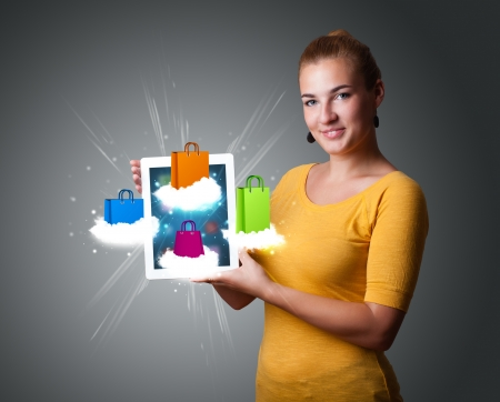 beautiful woman holding modern tablet with colorful shopping bags on clouds Stock Photo - 18529833