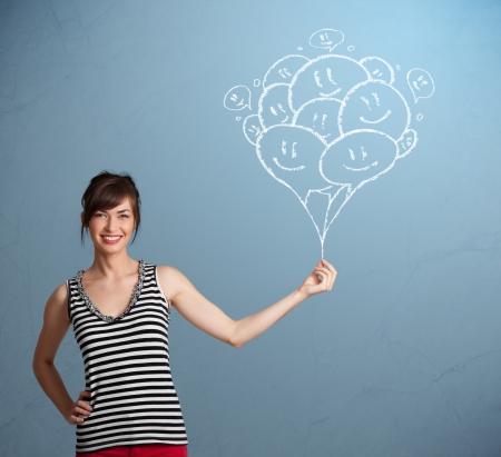 cara sonriente: Mujer joven feliz que sostiene los globos sonrientes de dibujo