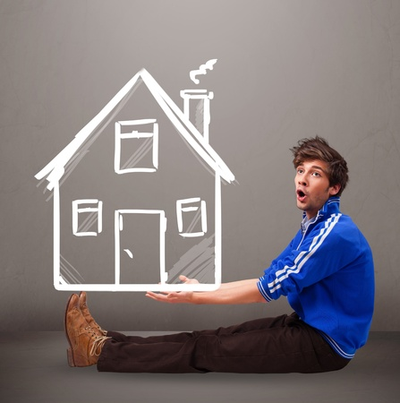Attractive young boy holding a huge drawn house Stock Photo - 18761435