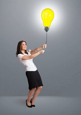 Pretty young woman holding a light bulb balloon photo