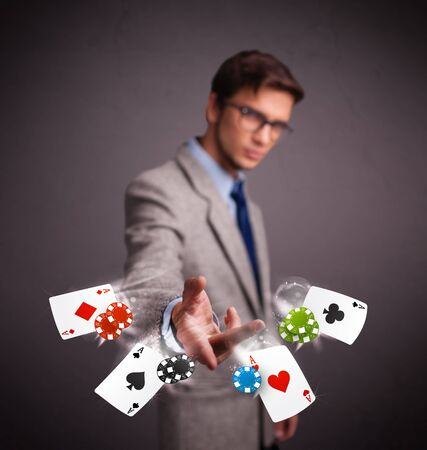 Handsome young man playing with poker cards and chips photo