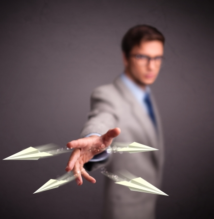Handsome young man throwing origami airplanes Stock Photo - 18919432