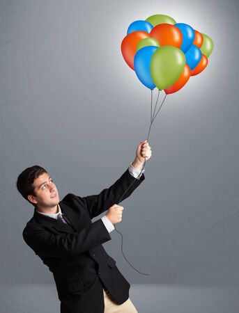 Handsome young man holding colorful balloons photo
