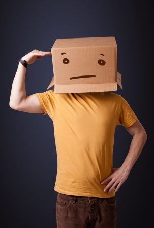 Young man standing and gesturing with a cardboard box on his head with straight face photo