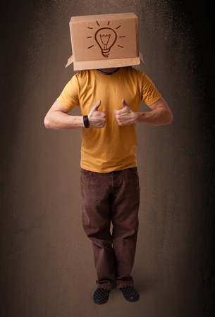 Young man standing and gesturing with a cardboard box on his head with light bulb photo