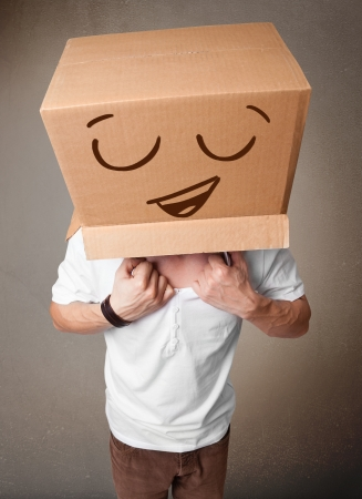 Young man standing and gesturing with a cardboard box on his head with smiley face photo