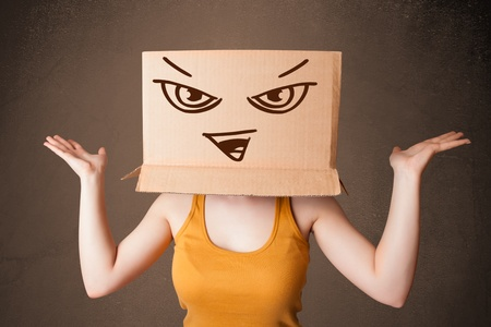 Young woman standing and gesturing with a cardboard box on her head with evil face photo