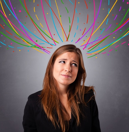 Pretty young girl thinking with colorful abstract lines overhead Stock Photo - 18971945