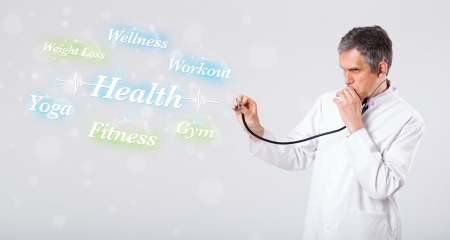 Elderly clinical doctor pointing to health and fitness collection of words photo