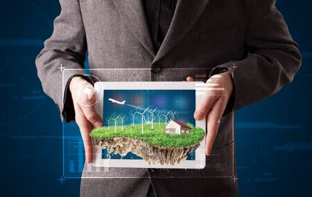 Young businessman presenting a perfect ecology land with a house and windmills photo