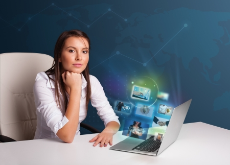Beautiful young girl sitting at desk and watching her photo gallery on laptop Stock Photo - 19124360
