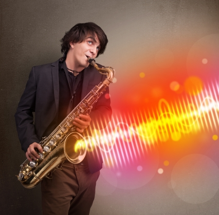 Attractive young man playing on saxophone with colorful sound waves photo