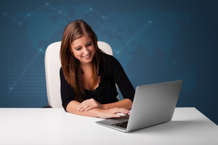 Pretty young woman sitting at desk and typing on laptop photo
