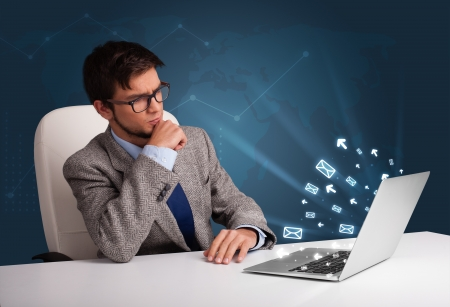 Attractive young man sitting at dest and typing on laptop with message icons comming out Stock Photo - 19292752