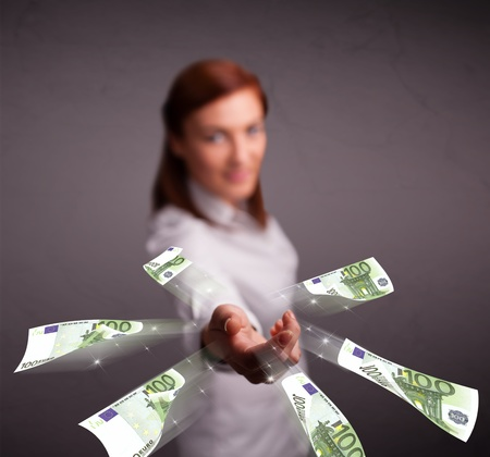 Pretty young woman standing and throwing money Stock Photo - 19292683