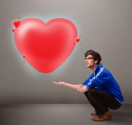 Handsome young man holding lovely 3d red heart photo