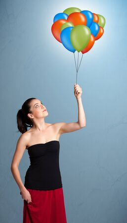 Pretty young woman holding colorful balloons photo