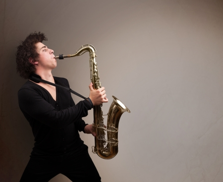 Handsome young musician playing on saxophone