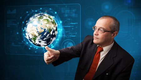 Businessman standing and touching high-tech 3d earth panel Stock Photo - 19294298