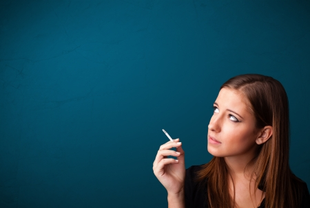 nicotine: Beautiful young woman smoking cigarette with copy space Stock Photo