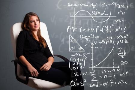 signos matematicos: Hermosa joven de la escuela piensa la chica acerca de los signos matem?cos complejos Foto de archivo