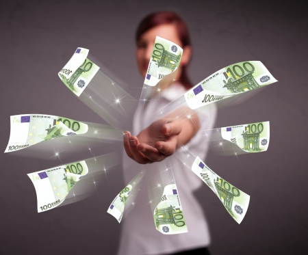 Pretty young woman standing and throwing money Stock Photo - 19374309