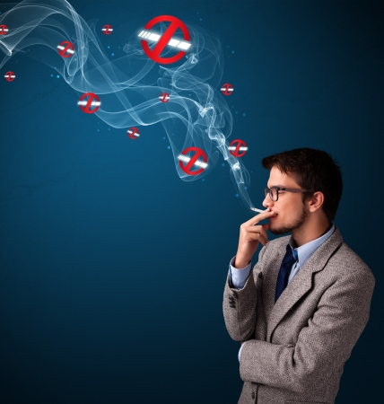 dangerous man: Attractive young man smoking dangerous cigarette with no smoking signs Stock Photo