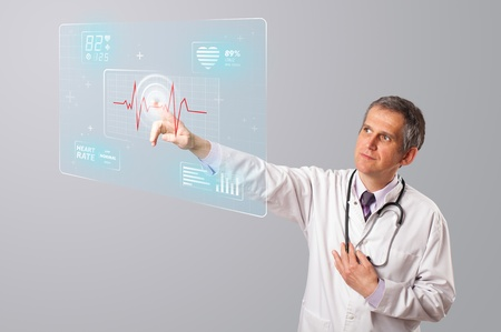 Middle aged doctor standing and pressing modern medical type of button Stock Photo - 19374379