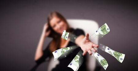 Pretty young woman sitting and throwing money Stock Photo - 19513921