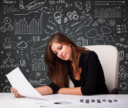 Pretty young businesswoman sitting at desk with business scheme and icons photo