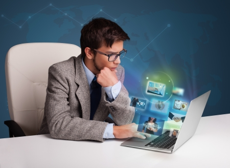 Attractive young man sitting at desk and watching his photo gallery on laptop Stock Photo - 19514227