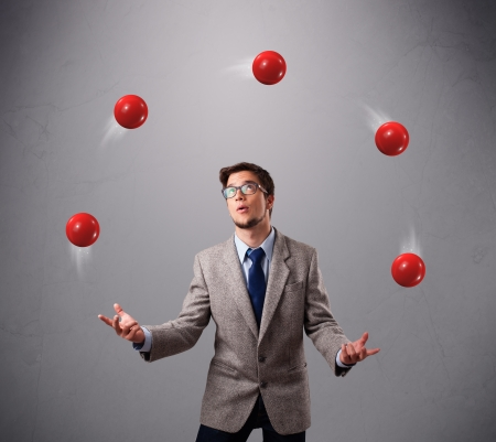 balance ball: handsome young man standing and juggling with red balls Stock Photo