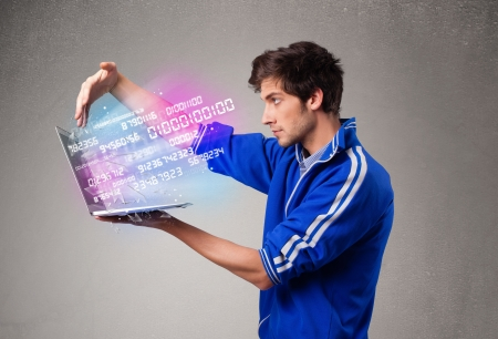encode: Casual young man holding laptop with exploding data and numbers Stock Photo