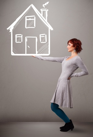 Beautiful young lady holding a huge drawn house Stock Photo - 19514416