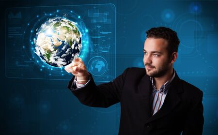 Handsome young businessman touching high-tech 3d earth panel photo