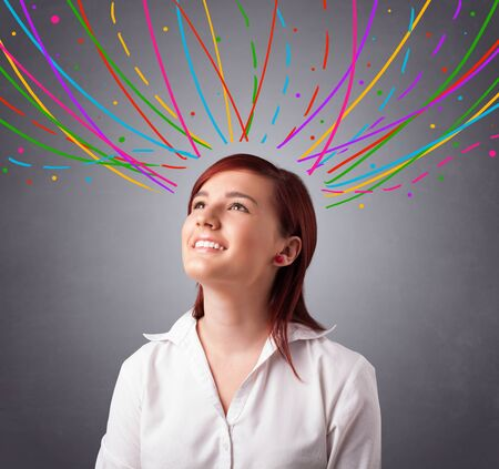 Pretty young girl thinking with colorful abstract lines overhead Stock Photo - 19540082