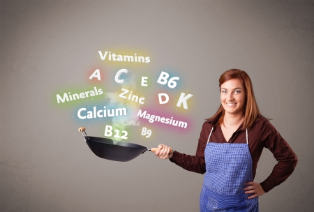 vitamins: Pretty young woman cooking vitamins and minerals