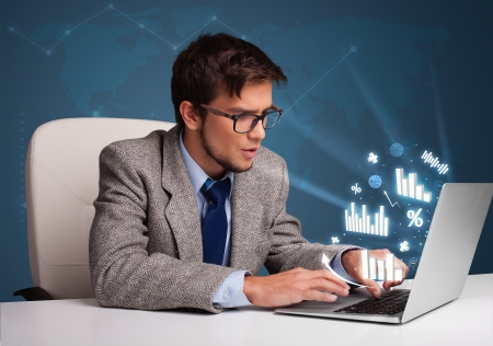 Young man sitting at desk and typing on laptop with diagrams and graphs comming out Stock Photo - 19539661