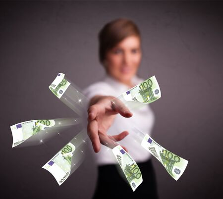 Pretty young woman standing and throwing money Stock Photo - 19540092