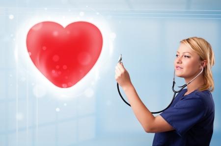 Pretty young nurse healing a red heart photo