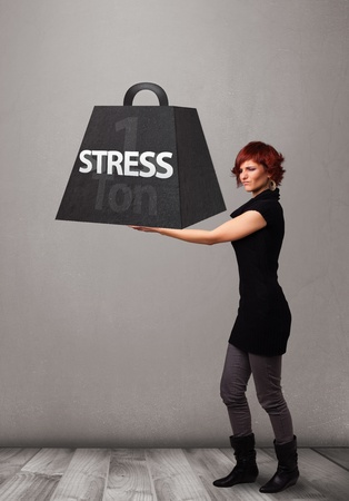 ton: Attractive young woman holding one ton of stress weight Stock Photo