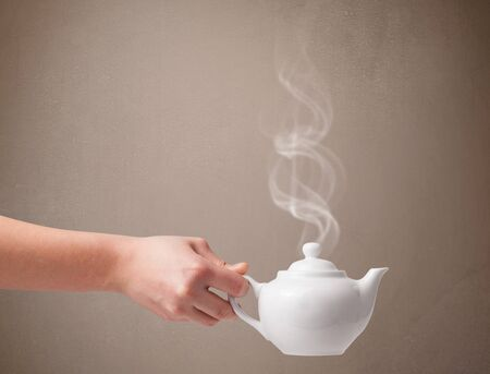 Tea pot with abstract white steam, close up photo